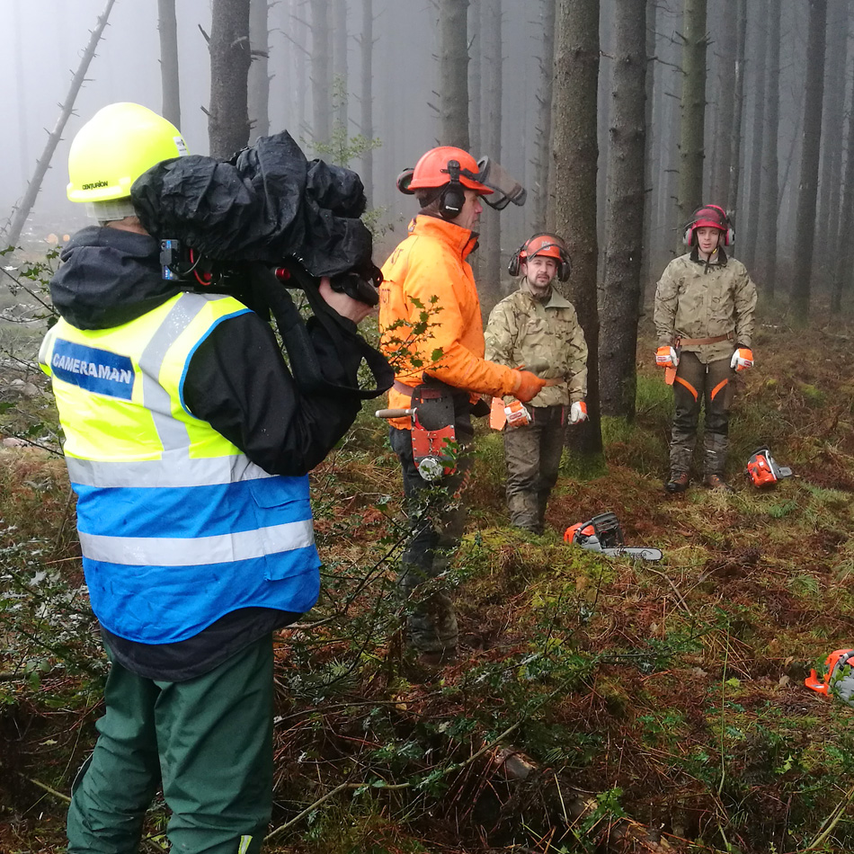 Filming a corporate video in a forest for a chainsaw training company